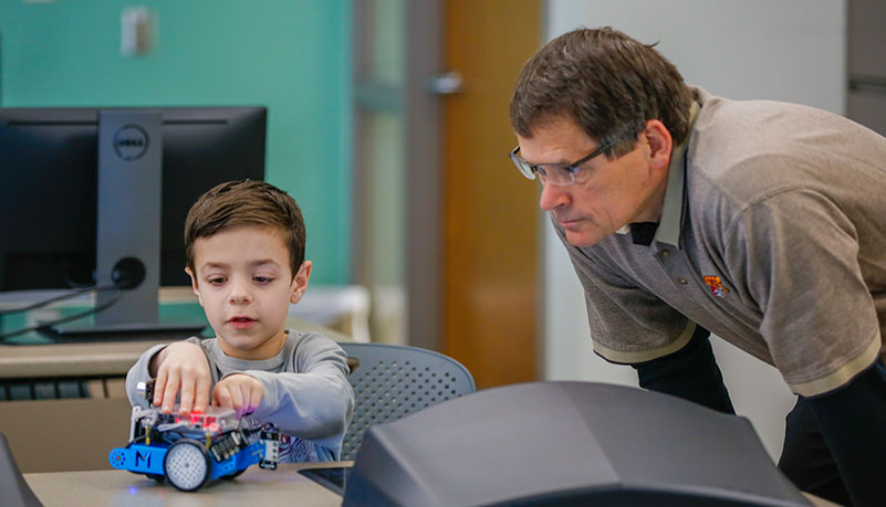 Professor watching child with a robot