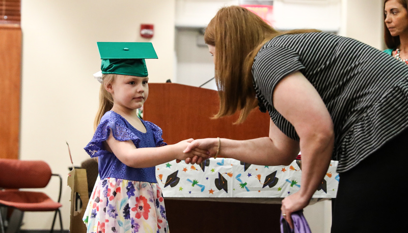girl receives her pre-school diploma