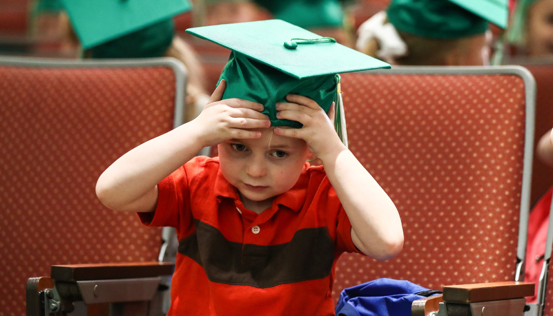 Boy adjusts his cap