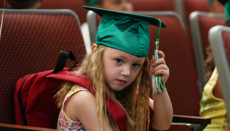 Girl adjusts his cap