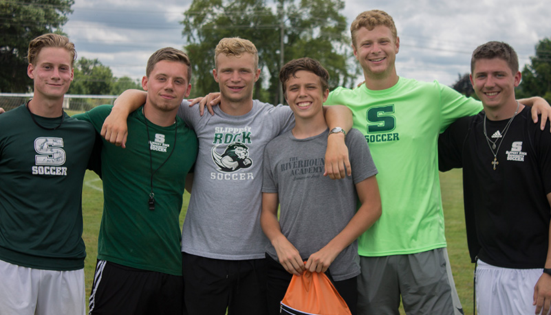 Men jubilantly standing with each other smiling at the camera wearing SRU apparel.