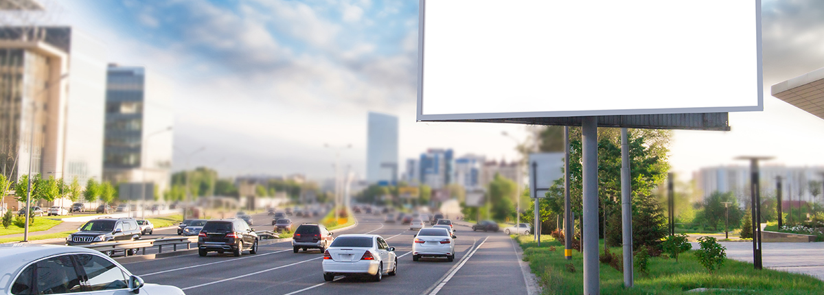 Image of a blank billboard on a busy highway with a city in the background