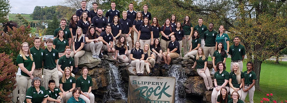 A group of SRU athletic trainers posing in front of the waterfall on campus