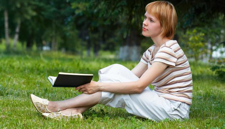 Student reading outdoors