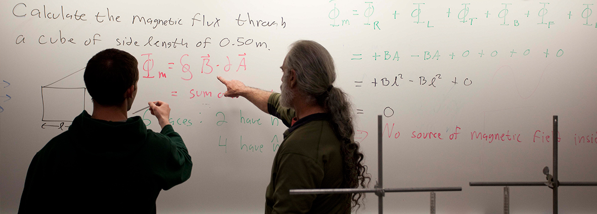 Student works on equation with professor