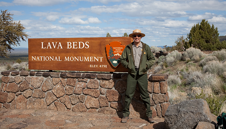 Park ranger in front of sign