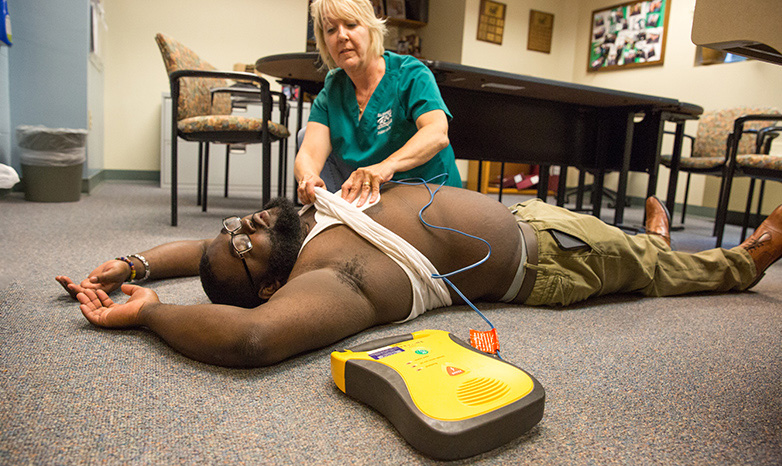 nurse using and AED defibrilator on patient