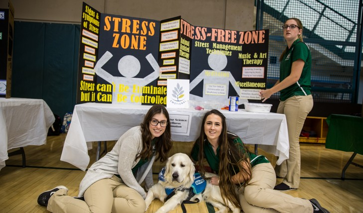 students pose for picture with support dog