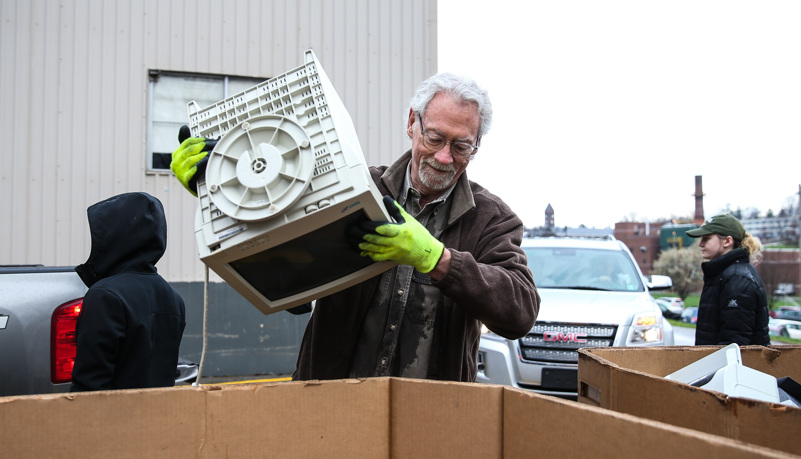 Man putting a comupter into a recycling box