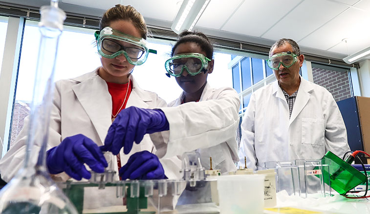 Students in a lab being supervized by a professor