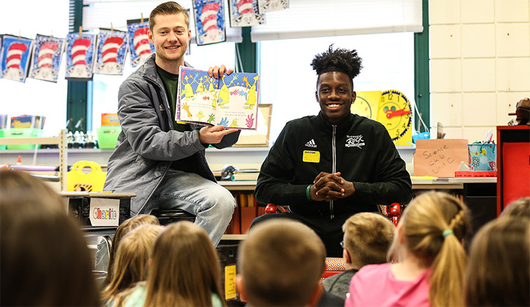 Football players reading to second graders