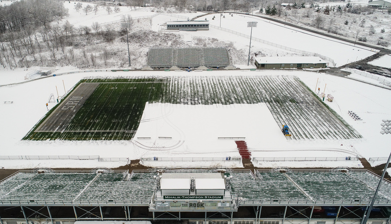 Matainence removes the snow from the football field