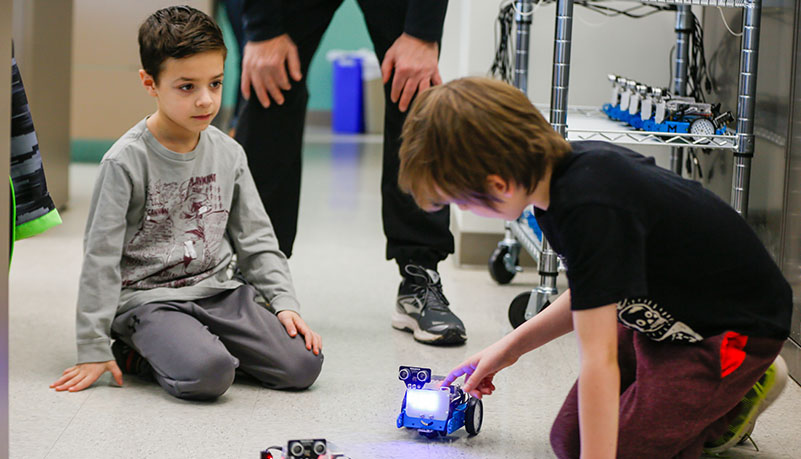 two children playing with robot