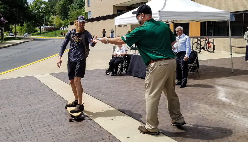 President handing put a snack bar to a student on a skateboard