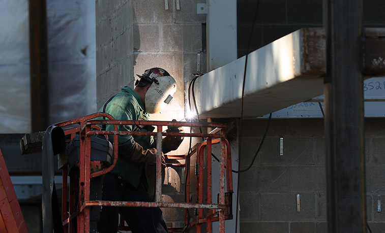 Welding working on the steel structure of Miller Auditorium