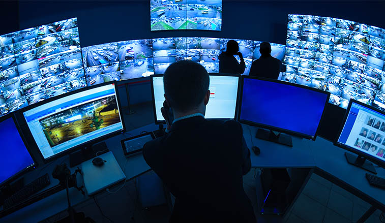 Man working behind CCTV monitors