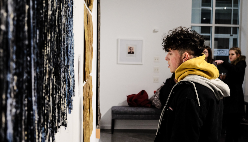 a man looking at art on display