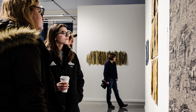 a woman looking at art on display