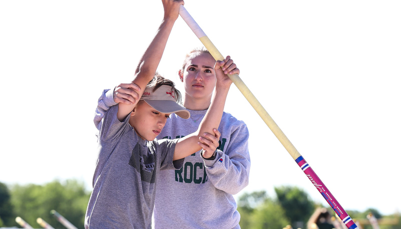 SRU student helps a high school athlethe with hand placement on a pole vault pole