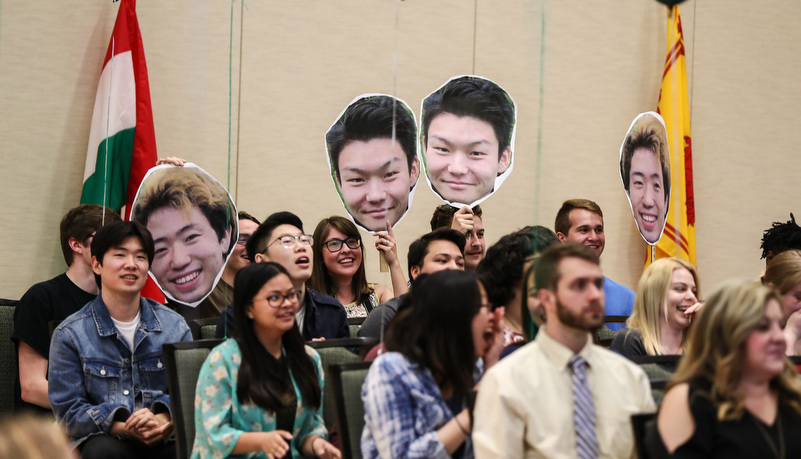 students hold up cutouts of their friends as they graduate
