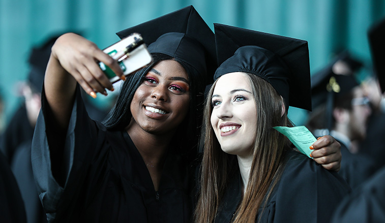 Two students stop for a photo before they graduate