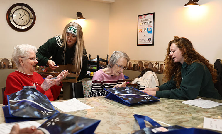 Second from left, Slippery Rock University students Gabrielle Cunningham and, far right, Rosemary Franklin help residents at the Home 2 Me assisted-living facility in Slippery Rock gather items for care packages that will be distributed to homeless people in Pittsburgh.