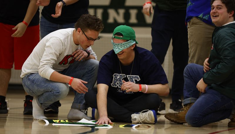 Blindfolded Kappa Sigma students using touch to piece back together torn papers