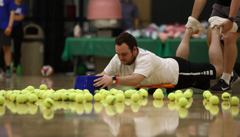 Guy scooping tennis balls in a game