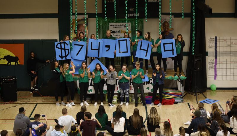 Students holding signs to show total amount fundraised of $74,049