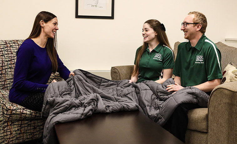 Students and a professor discuss the benefits of a weighted blanket