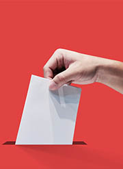 Hand placing a ballot in a ballot box